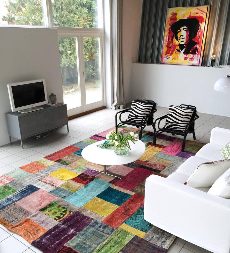 Alfombra patchwork - turkiet multicolor cuadrada en salón.